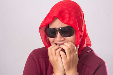 Portrait of Asian muslim lady wearing black sunglasses in red suit and hijab looked worried and afraid of something bad, biting her nails