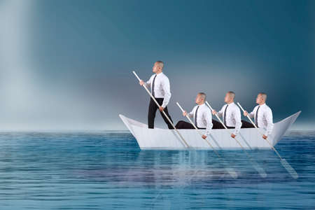 Leader businessman ;ead his team paddling on boat of paper in the ocean, teamwork challenge in business, pursuing success concept