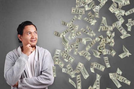 Retrato de feliz joven asiático sonriendo y pensando soñando lluvia de dinero. Concepto económico de inversión de riqueza