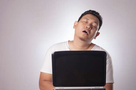 Portrait of Asian man wearing casual white shirt looked tired sleepy overworked in with laptop, midnight working concept Imagens