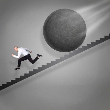 Businessman running down the stairs runaway from falling ball stone, failure in business concept Reklamní fotografie