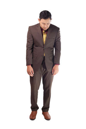 Portrait of Asian businessman sad and look down, concept of business failure and guilty feeling, full body portrait isolated on white