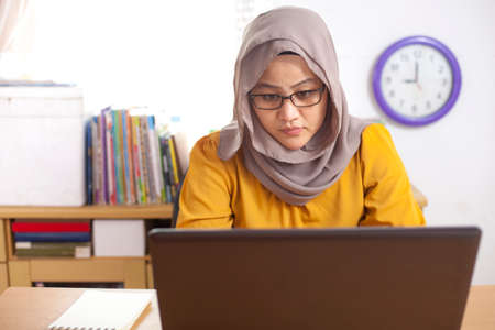 Portrait of Asian muslim businesswoman working on laptop at the office, smiling happy expression Stock Photo - 115656093