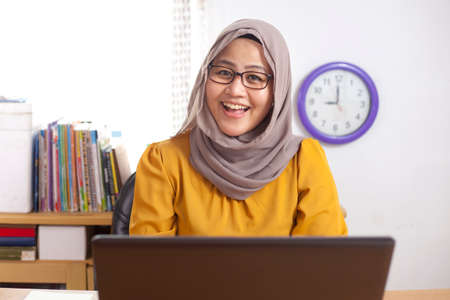 Portrait of Asian muslim businesswoman working on laptop at the office, smiling happy expression Stock Photo