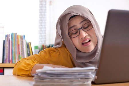 Portrait of Asian muslim businesswoman tired sick stress shocked headache gesture because of more paper work to do, overworked at the office