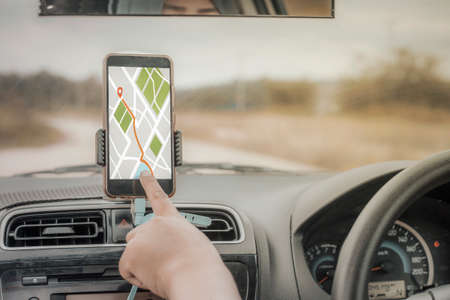 Car driver using smart phone with GPS map navigation while driving, car sharing app concept