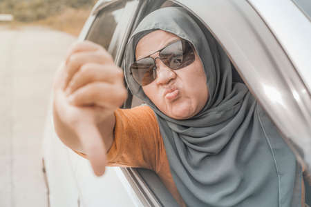 Portrait of Asian muslim lady driver getting mad and angry from the traffic, screaming and showing rude gesture from her car Stock Photo