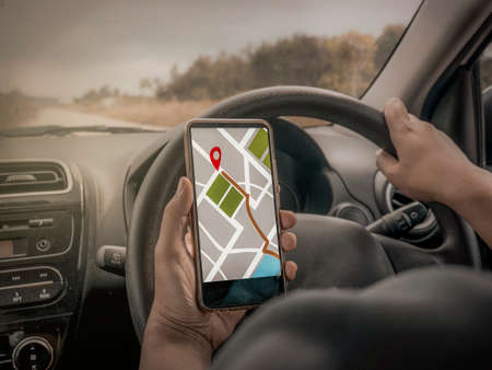 Car driver using smart phone with GPS map navigation while driving, car sharing app concept Banco de Imagens