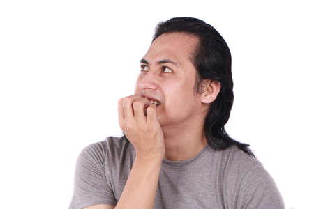 Portrait of young funny Asian man crying and  biting his nails as if he is worried afraid of something bad
