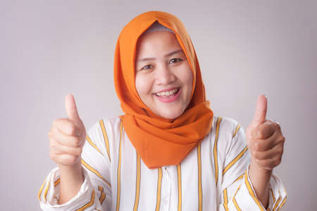 Portrait of young Asian muslim lady wearing hijab shows thumbs up gesture, smiling happy face, approved OK sign Imagens