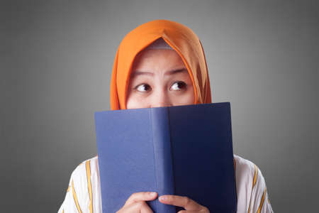Portrait of young muslim businesswoman wearing hijab reading book, thinking and hiding her face behind the book
