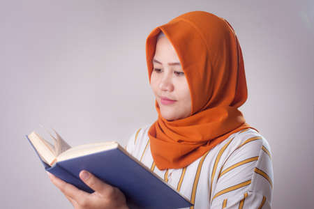 Portrait of young muslim businesswoman wearing hijab reading book