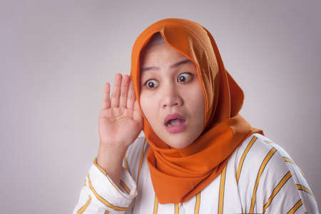 Portrait of Asian muslim lady wearing hijab hold her hand on ear trying to listening carefully to the conversation of someone, shocked curious facial expression Stock Photo