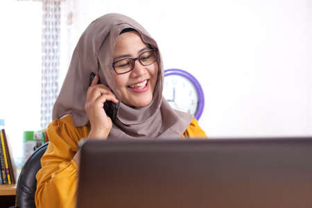 Portrait of muslim businesswoman wearing hijab in office talking on phone, happy smiling expression having good news Banque d'images - 117970814
