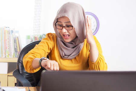 Young Asian businesswoman wearing hijab worried by time when looking at her wristwatch. Work deadline stress at the office Stock Photo