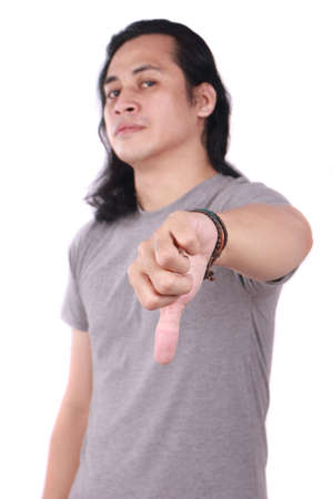 Portrait of good looking long haired young Asian man shows thumbs down gesture with his finger isolated on white Banco de Imagens