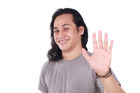Portrait of good looking long haired young Asian man shows hi or high five gesture with his finger isolated on white