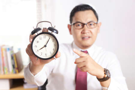 Young Asian businessman pointing at clock, angry expression. Time deadline concept. Man working in office