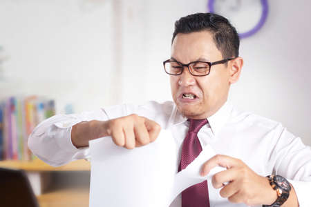 Portrait of angry mad young Asian businessman rip off contract paper, disappointed frustrated business worker
