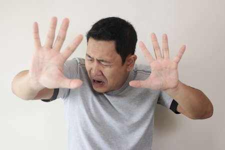 Photo image of crying sad young Asian man showing surrender gesture, hands raised up asking to stop bully on him, against white wall Stock Photo