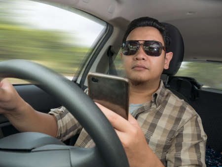 Male Asian driver reading message on smart phone while driving a car, dangerous traffic safety accident crash car insurance concept