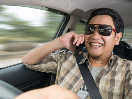 Male Asian driver making a call while driving a car, dangerous traffic safety accident crash car insurance concept