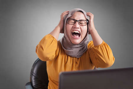 Portrait of angry stressed muslim businesswoman wearing hijab with mad insanity gesture Stock Photo