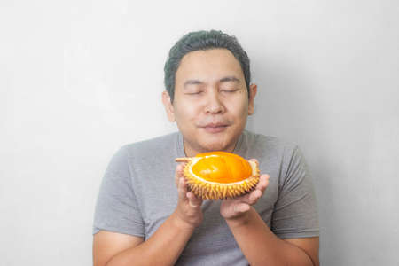 Portrait of funny Asian man enjoys yellow durian, king of fruit from Asia, stinky exotic food Banco de Imagens