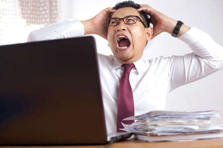 Portrait of angry depressed frustrated Asian businessman scream at the office for having stress overworked problems
