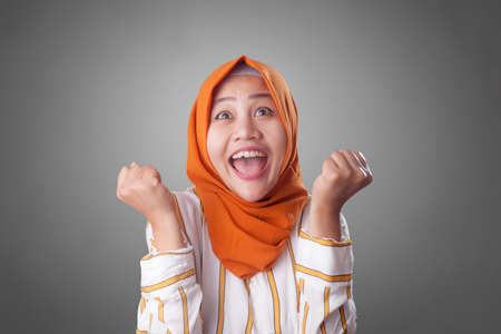 Portrait of success beautiful muslim businesswoman wearing hijab showing winning victory gesture over gray background Stockfoto