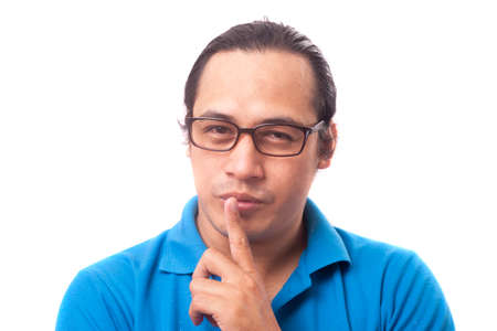 Portrait of young Asian man smiling and shows shushing gesture, as if he is telling be quiet keep it secret, isolated on white