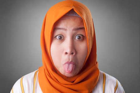 Portrait of Asian muslim woman shows tongue out, mocking grimacing face expression Reklamní fotografie