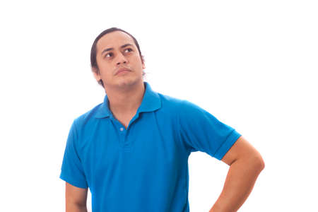 Young Asian man wearing casual blue shirt thinking, looking to the side. Close up body portrait isolated on white