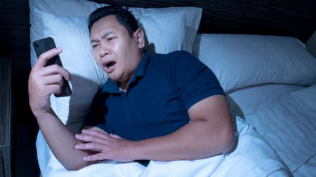 Receiving bad news on phone at midnight concept, Asian male shocked annoyed expression to have bad news on phone while lying on bed at midnight