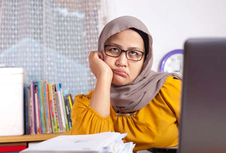 Portrait of Asian muslim businesswoman looking tired sleepy and lazy waiting for something in front of her laptop at the office