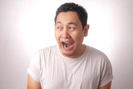 Portrait de drôle de jeune homme asiatique riant souriant et regardant sur le côté, sur fond blanc