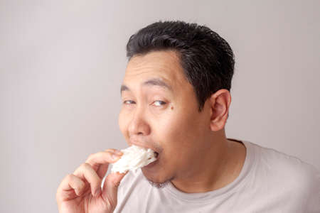Portrait of funny good looking Asian young man eating kerupuk. Kerupuk is Indonesian fish or prawn cracker.