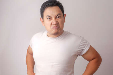 Photo image of funny Asian man showing cynical unhappy angry facial expression