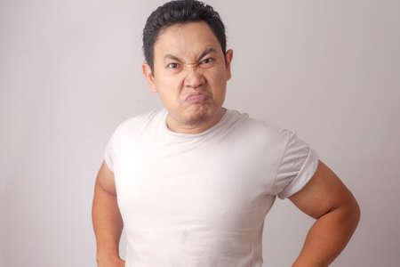 Zdjęcie przedstawiające zabawnego Azjatę pokazującego cyniczny, nieszczęśliwy, zły wyraz twarzy facial