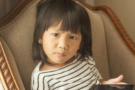 Portrait of Asian little girl plays with gadget smart phone, children with phone addict concept 스톡 콘텐츠