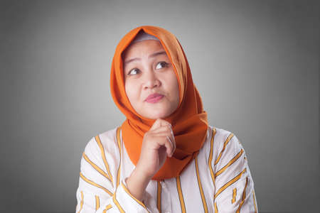 Asian muslim businesswomen wearing hijab with curiousity thinking expression. Having good idea. Close up head and shoulders