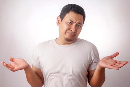 Image photo d'un homme asiatique drôle avec un geste d'épaule vers le haut, montrant je ne sais pas ou le rejet