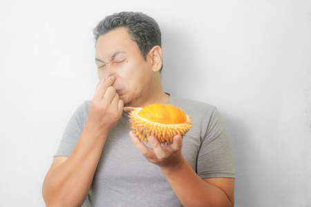 Portrait of funny young Asian man holding stinky durian fruit, bad smell want to puke gesture Standard-Bild