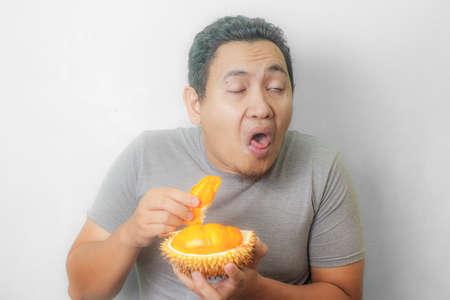 Porträt eines lustigen jungen asiatischen Mannes, der stinkende Durianfrucht hält, schlechter Geruch möchte Geste kotzen