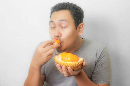 Il ritratto di un uomo asiatico divertente gode di durian giallo, re di frutta dall'Asia, cibo esotico puzzolente Archivio Fotografico