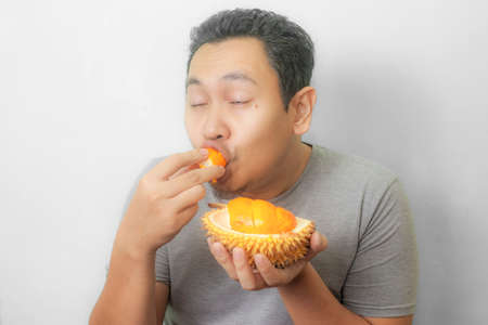 Portrait of funny Asian man enjoys yellow durian, king of fruit from Asia, stinky exotic food Standard-Bild
