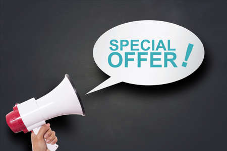 Hand holding megaphone agains blackboard with big sale special offer, announcement marketing concept