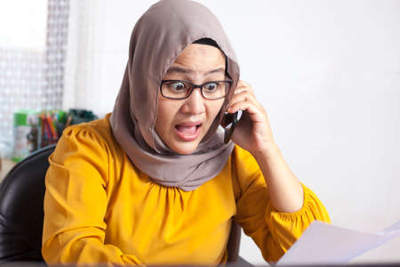 Portrait of young Asian muslim businesswoman shocked by phone call, worried expression. Woman working at office
