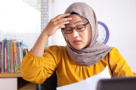 Portrait of Asian muslim businesswoman working on laptop at the office, tired sick stress headache gesture because of overworked, ramadan fasting concept Imagens