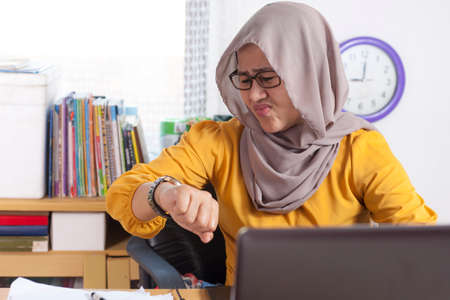 Young Asian businesswoman wearing hijab worried by time when looking at her wristwatch. Work deadline stress at the office. Working during Ramadan waiting for fast breaking time